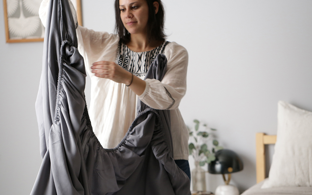 A woman folding a fitted sheet.