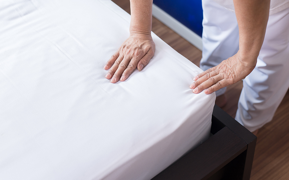 A person smoothing a fitted sheet onto a bed.
