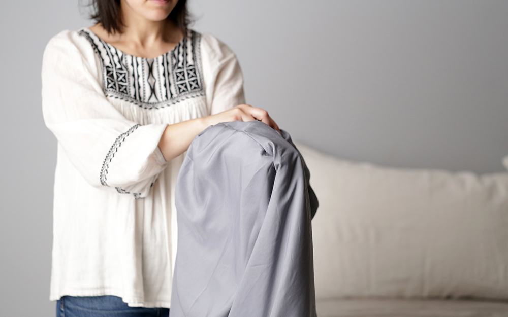 A woman looping a fitted sheet over its own corner.