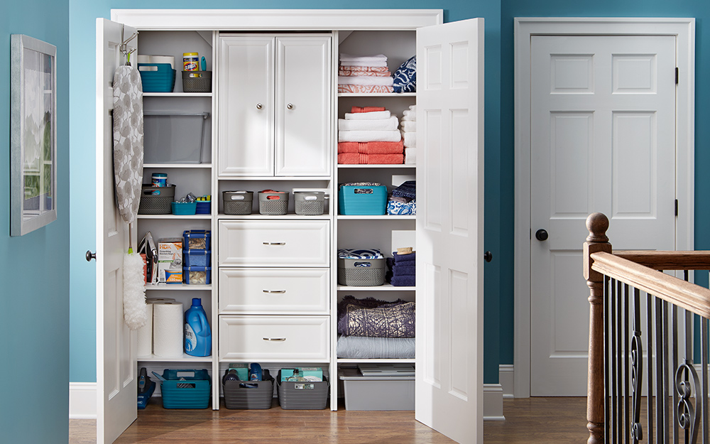 A linen cabinet with open doors and linens on shelves.