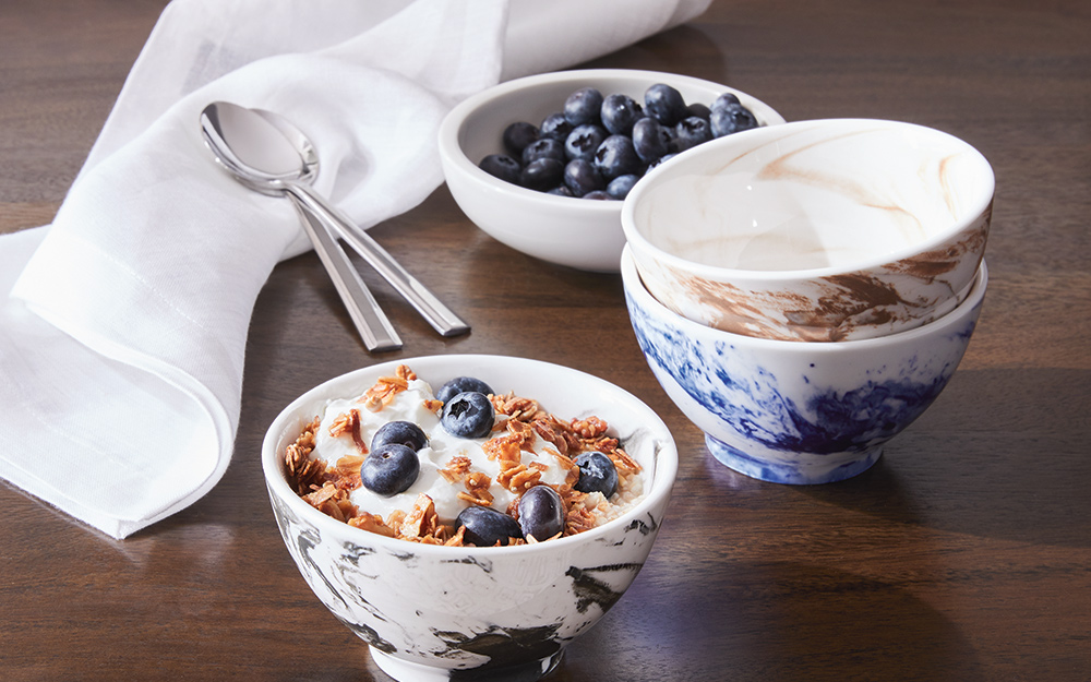 A white napkin on a table with cereal bowls and spoons