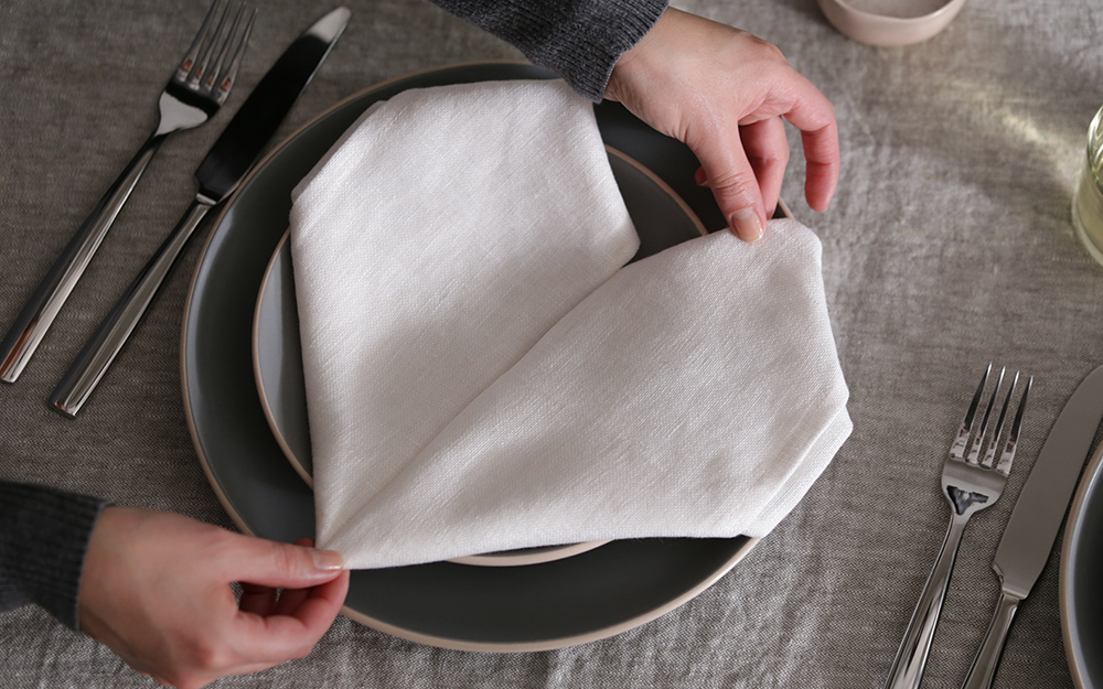 A person completing a heart napkin fold on a dinner plate