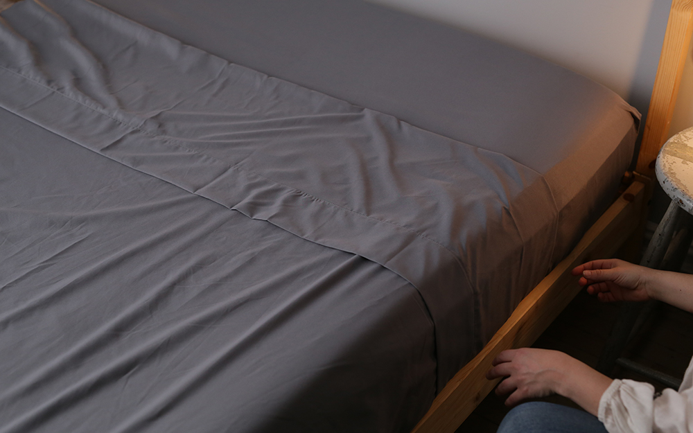 A person tucking in grey sheets on a bed