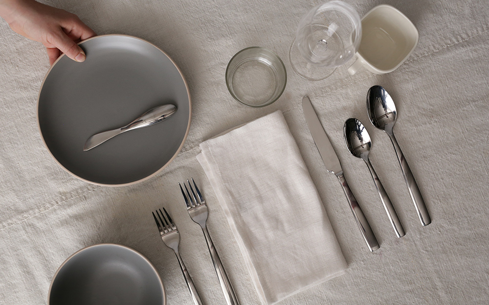 A person setting a table with grey dishes and flatware.