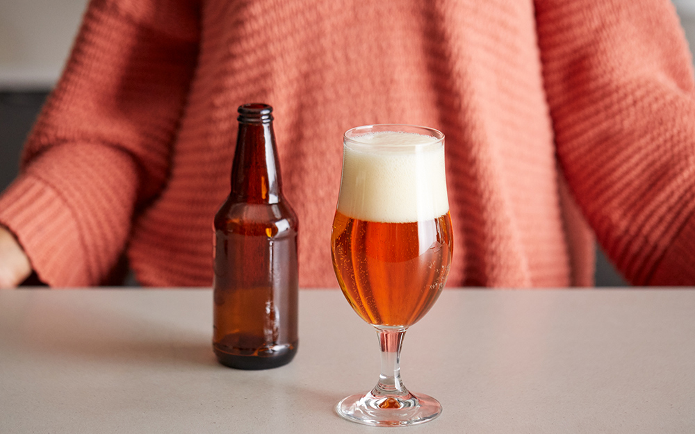 A filled tulip style beer glass on a counter