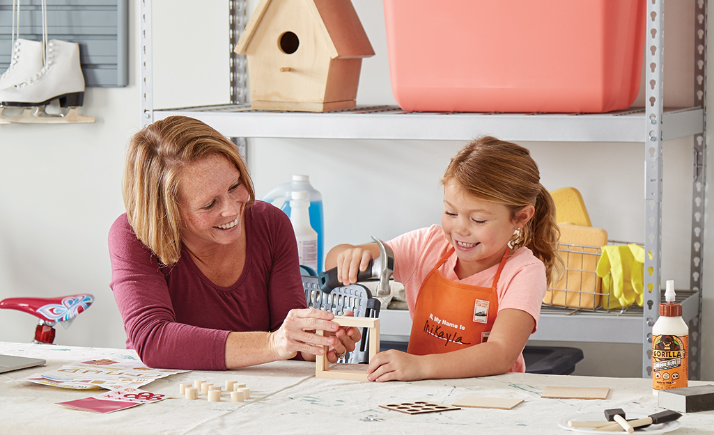 A woman helping a child tap nails into the tic-tac-to project.