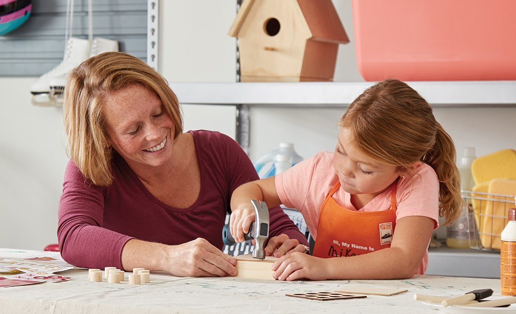 A woman helps a child attach the bottom of the tic-tac-toe project.