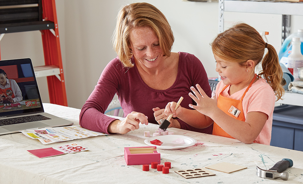 A woman helps a child paint the tic-tac-toe project.