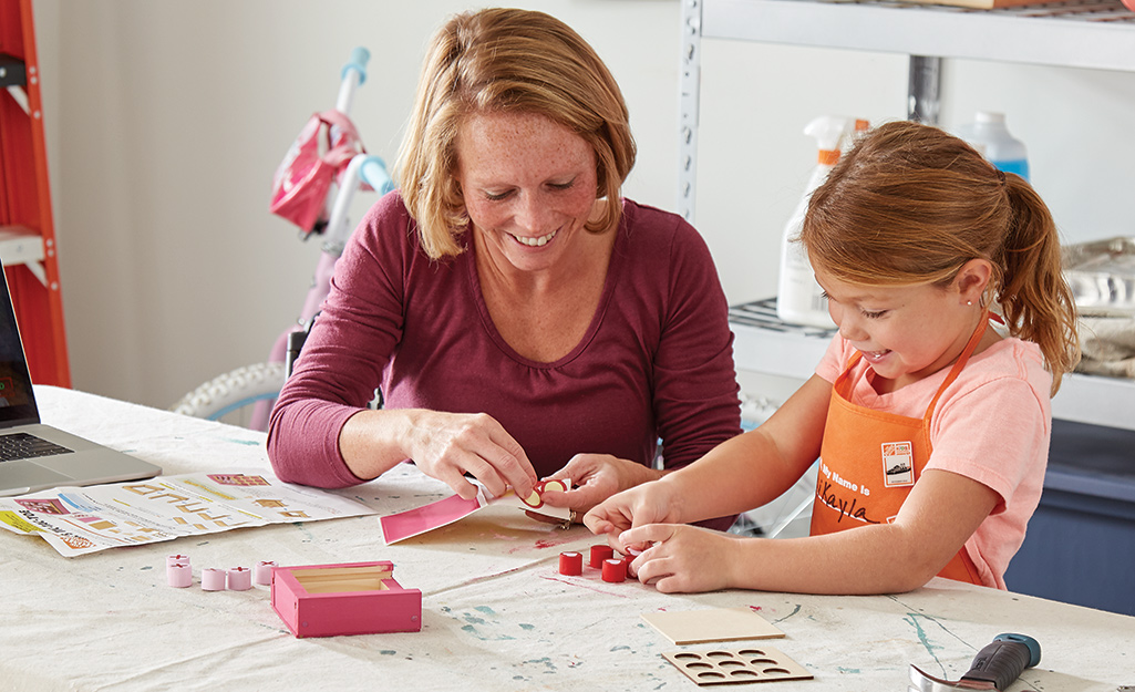 A woman helps a child attach stickers to tic-tac-toe pieces.