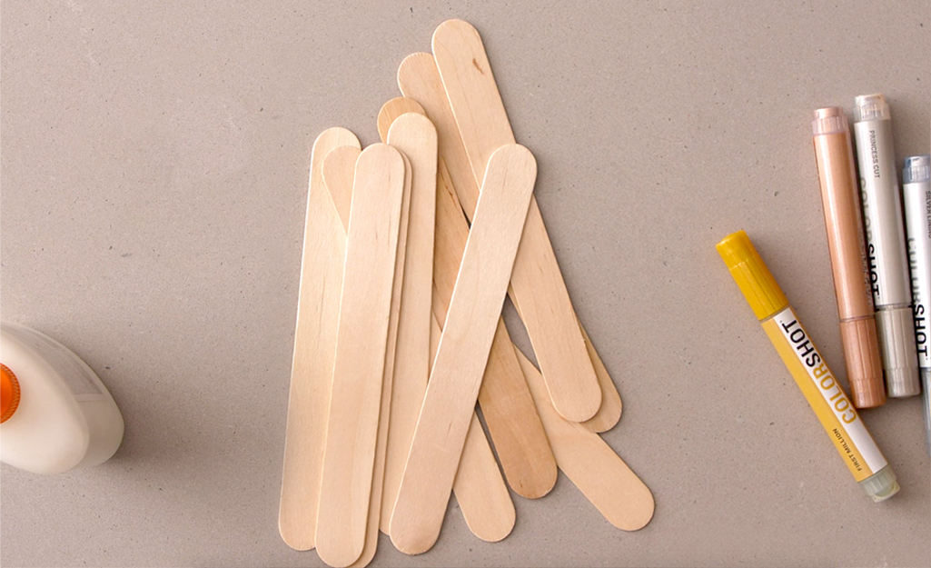 Popsicle sticks, markers and glue are gathered on a counter.