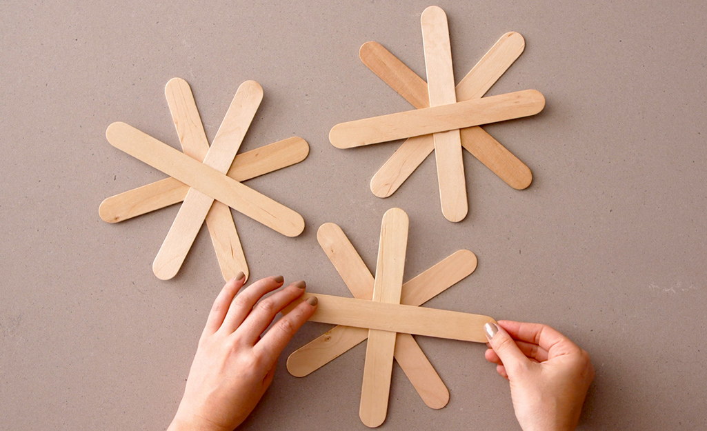 Popsicle sticks being glued to one another to create stars.