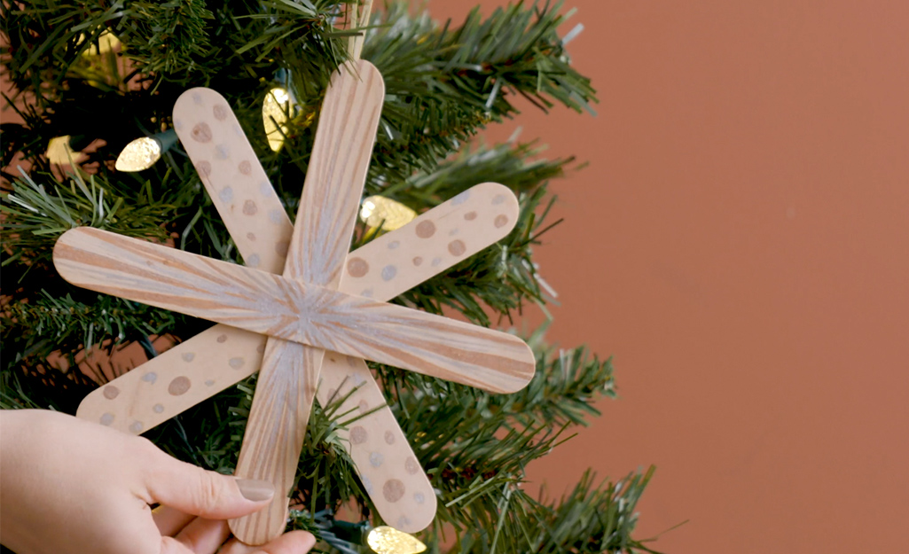 A DIY star ornament being placed on a Christmas tree.