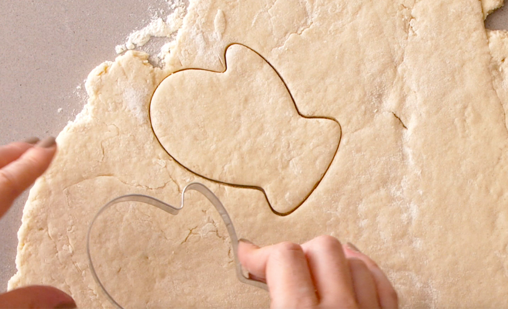 A person uses cookie cutters to cut shapes in dough.