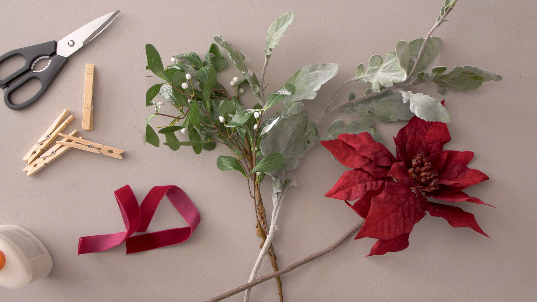 Fake poinsettias, ribbon, clothespins and other supplies.