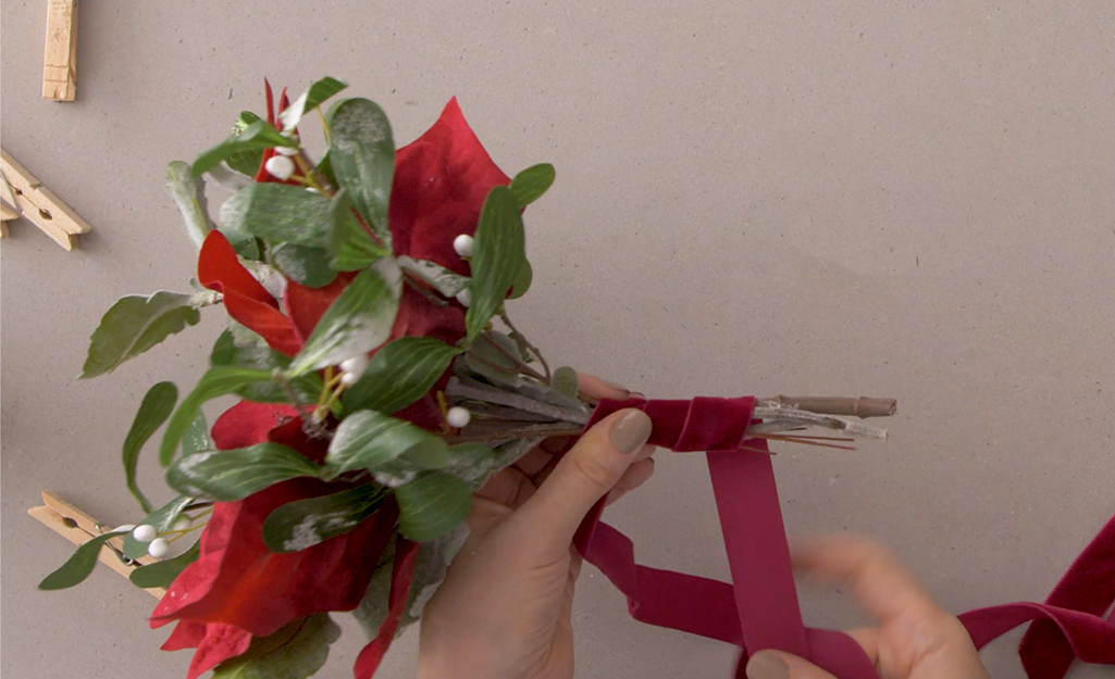 Maroon colored ribbon is wrapped around a bouquet.