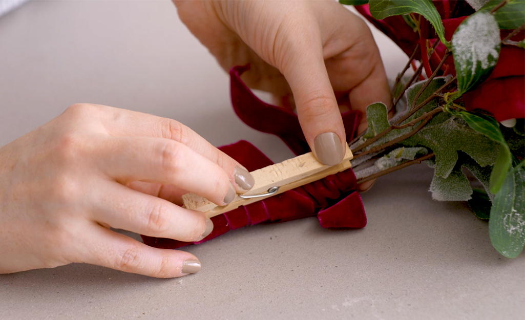 A clothespin being attached to the back of floral bouquet.