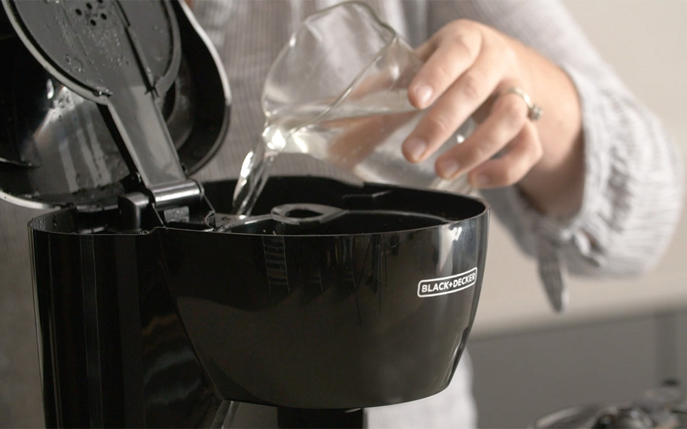 A person adding vinegar to a water reservoir of a coffee maker.