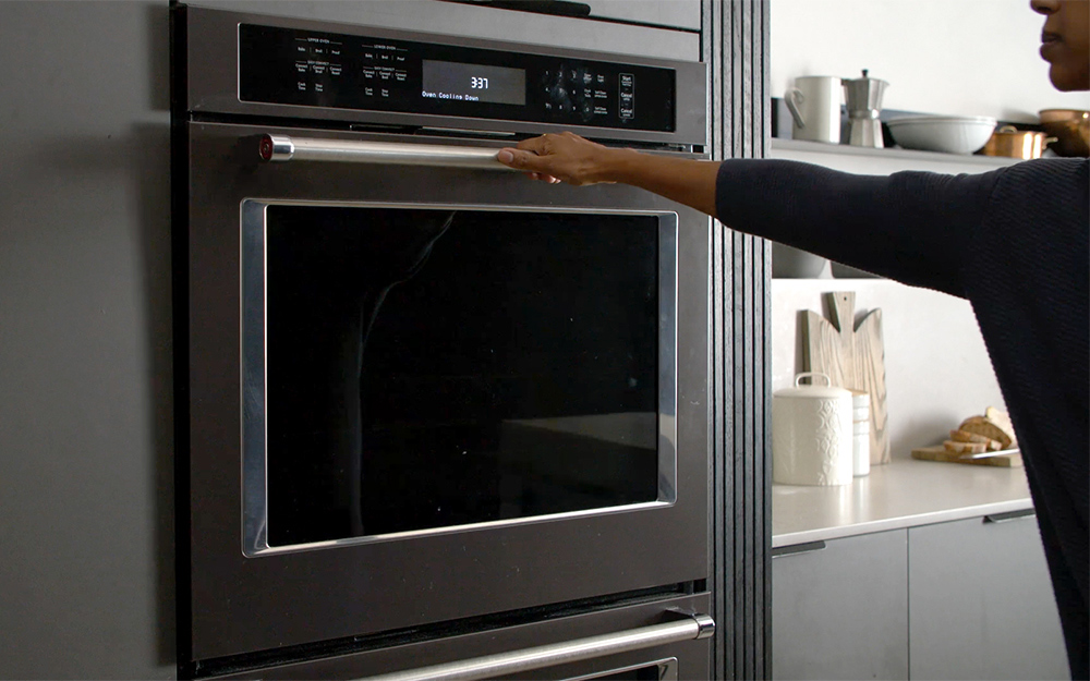 Person closing a self-cleaning oven.