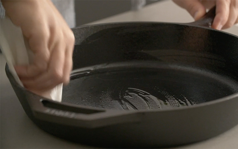 A person oiling a cast-iron skillet.