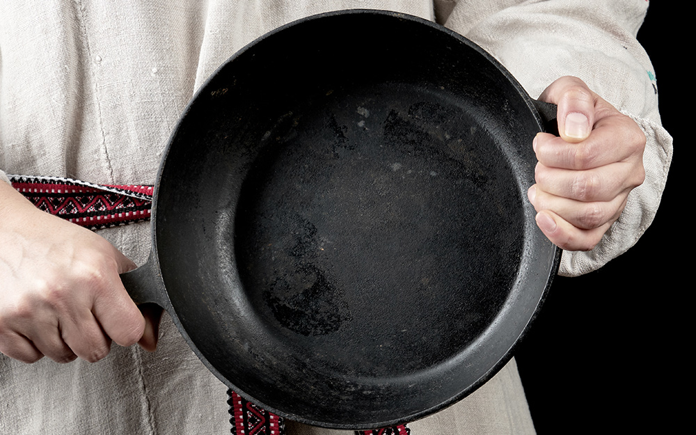 A person holding a cast-iron pan with a seasoned surface.
