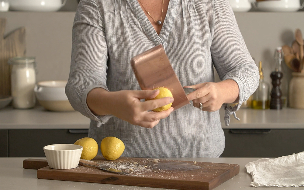 Person rubbing lemon on a copper pan.