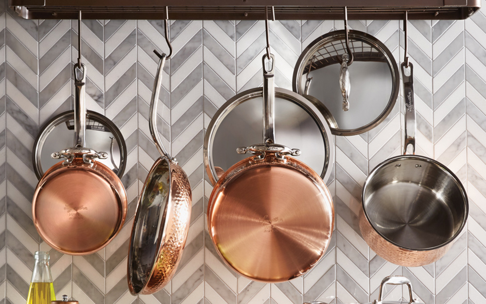 Copper pans hanging on a pot rack against a tile kitchen backsplash.