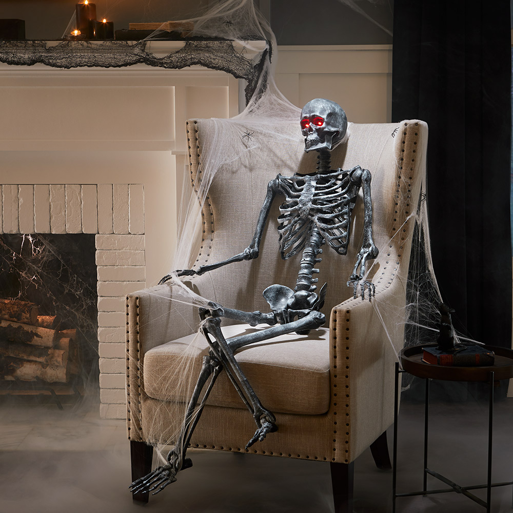 A skeleton decoration sits in an armchair.