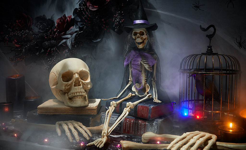 A halloween side table display with skeletons, string lights, candelabras and other trinkets