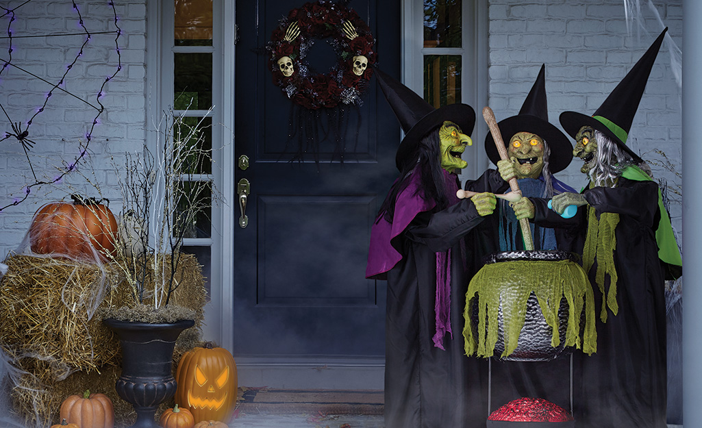 A Halloween display of pumpkins and witches on a porch.