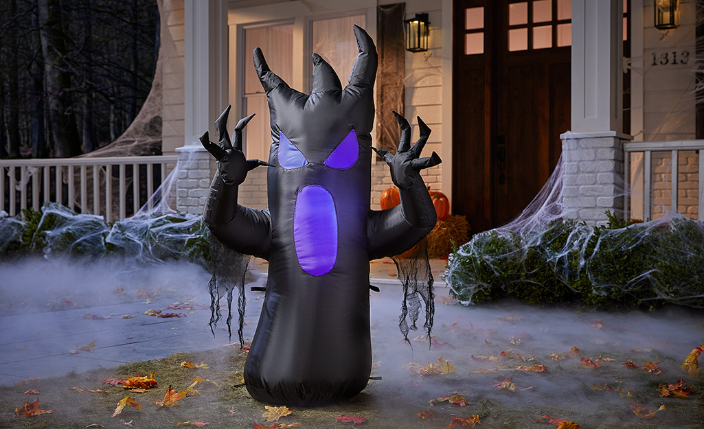 A spooky black and purple tree inflatable displayed in a yard.