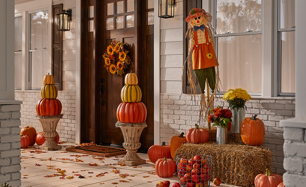 A front porch decorated in pumpkins and a friendly scarecrow.
