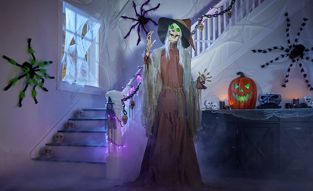 Giant fake spiders and a witch stand near a stairwell.