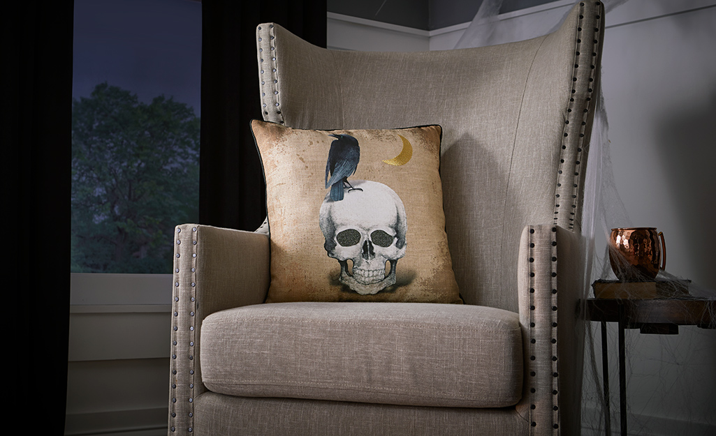 An armchair with a skeleton themed throw pillow.