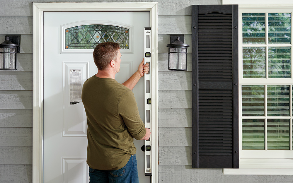 A man test fitting the frame of a home entryway.