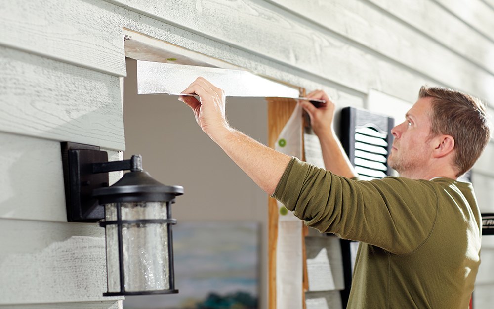 A man adjusting the moulding on the frame of a home entryway.