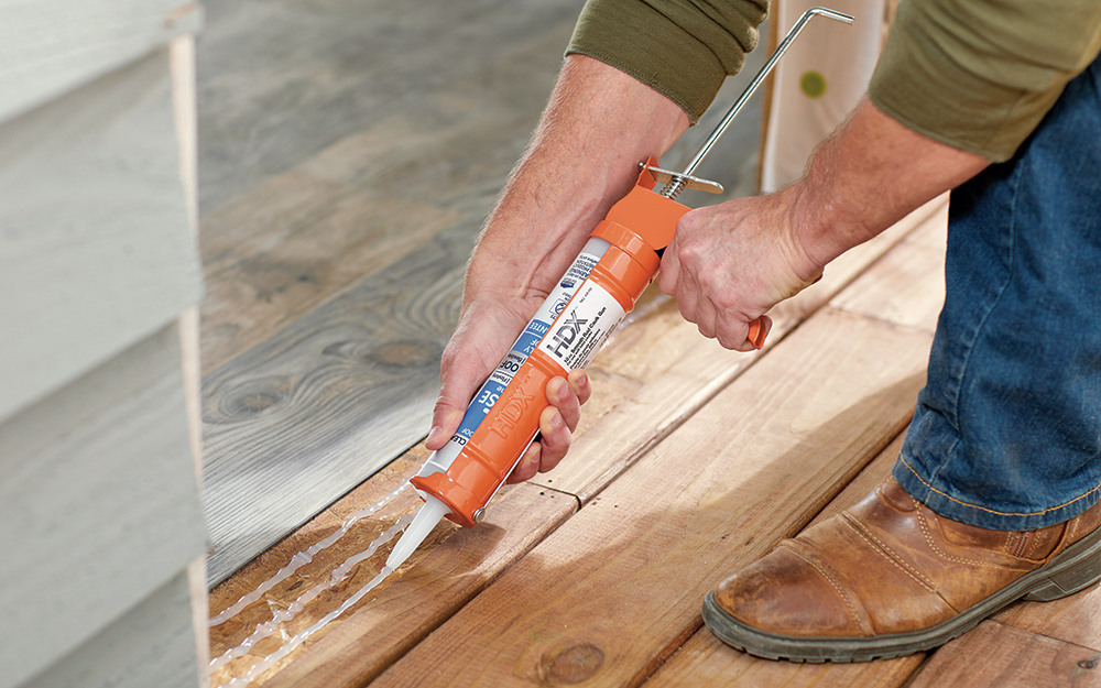 A man caulking the frame of a home entryway.