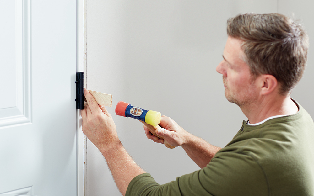A man shimming a new entry door inside the home.
