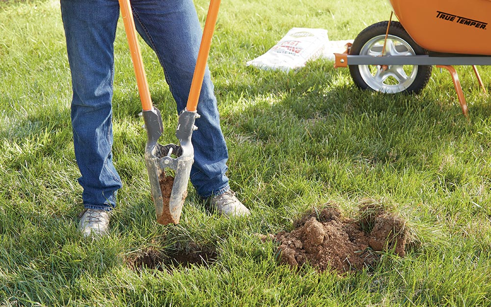 a person using a hole digger to prep the ground for flag pole installation