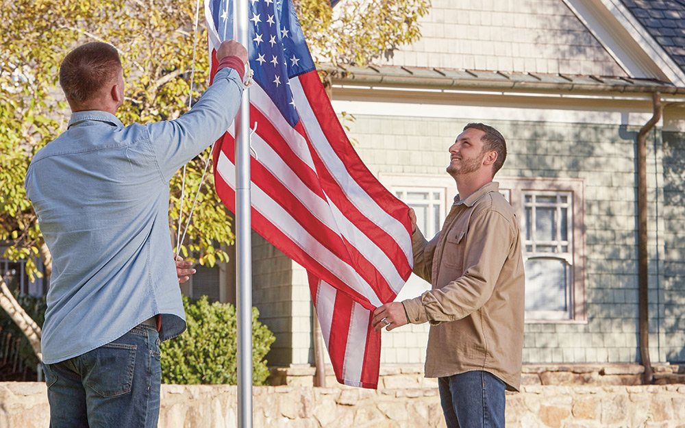 two people raising a flag on a newly installed flag pole