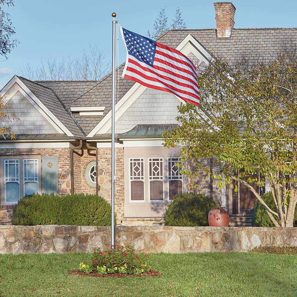 A front yard featuring a flag hanging from a flagpole