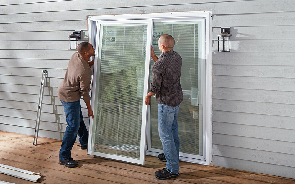 Two people positioning a new sliding door in a frame opening