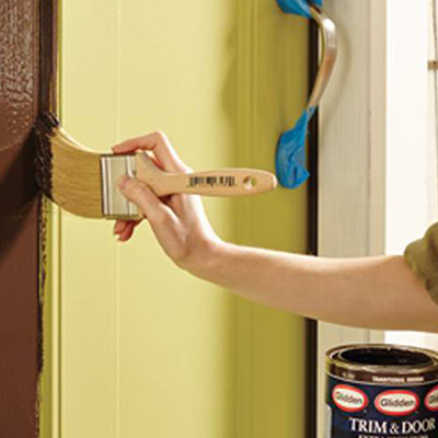 A person paints a door jamb with a paintbrush.