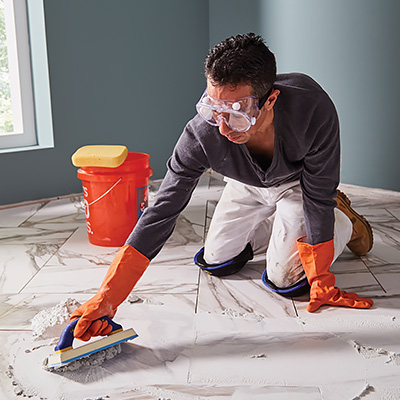 A person using a grout float to apply grout to tile.