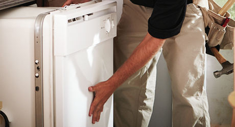 A person handling a dishwasher before installation