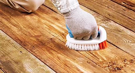 a person wearing protective gloves uses a small brush to scrub deck boards