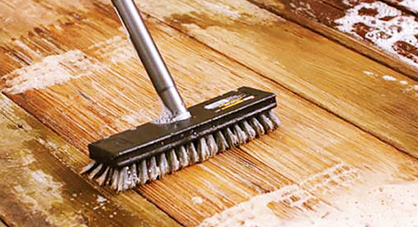 a large brush sweeps cleaner over deck boards