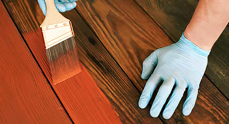A person applies stain to a deck with a brush