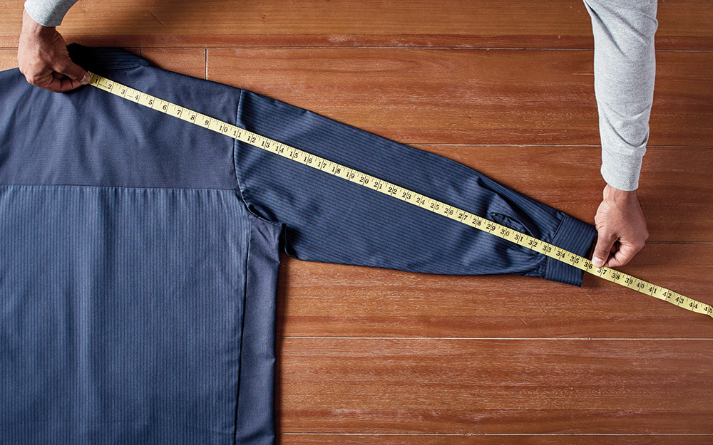 A person measures the sleeve length of a work shirt.