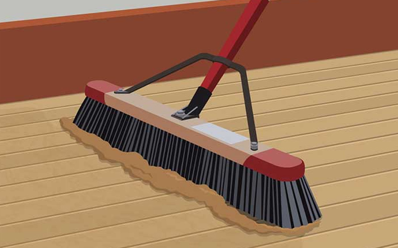 An illustration shows dust on a hardwood floor being swept by a broom.