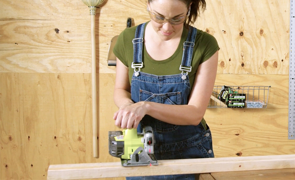 A worker trims studs for the DIY dog house.
